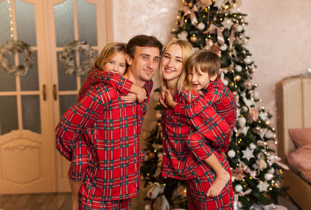 Big four members family in red pajams. Daddy mommy and two children spending x-mas time together piggyback riding and having fun at home