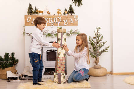 Cute happy excited children, boy and girl, sister and brother build a tower of Christmas gifts, play in a bright, cozy room with New Year's decor and a fireplace. Family holiday Stock Photo