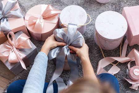 Female decorating christmas presents gift box, Ties ribbon bows. Collection in pastel gray and coral colors. For christmas or new year concepts