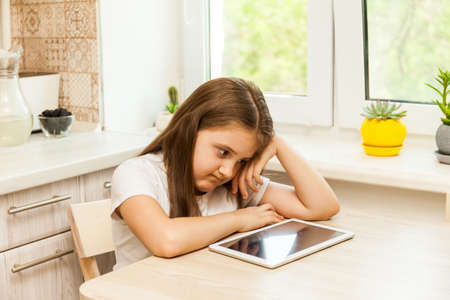 Little Upset and angry girl at home in the kitchen sitting at the table with tablet, Prohibition to use the gadget, limited time for games, gadget overuse concept Stock Photo