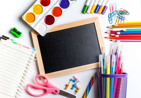 Blackboard in wooden frame surrounded by office and school supplies, notepad. Office and student gear over white background - Back to school concept