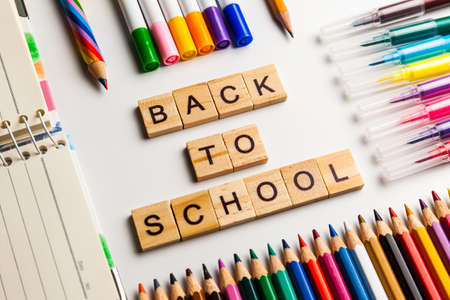 School office supplies, multicolored markers and pencils on a desk. Back to school text made with wooden blocks Stock Photo