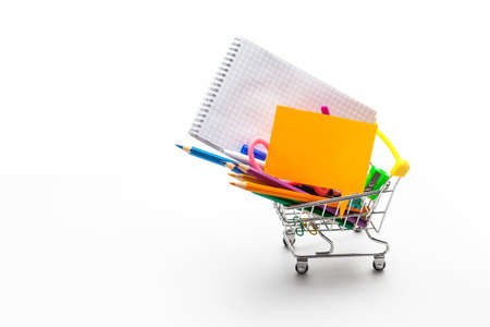 Shopping cart filled with multicolored school supplies isolated on a white background. Back to school concept