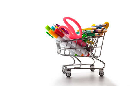 Shopping trolley filled with multicolored school supplies on a white background. Back to school concept Stock Photo