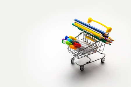 Shopping trolley filled with multicolored school supplies isolated on a white background. Back to school concept
