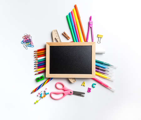 Blackboard in wooden frame surrounded by office and school supplies. Office and student gear over white background - Back to school concept Stock Photo