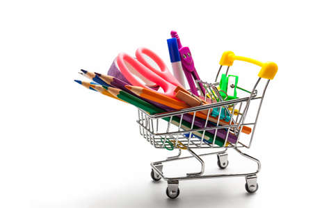 Shopping cart full of stationery or office supplies on white background. Back to school concept. Stock Photo