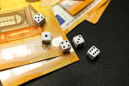 White Gaming dice and money on dark table. Money gambling concept, euro currency rate