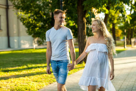 happy young pregnant woman with her husband walking in a city park Stockfoto