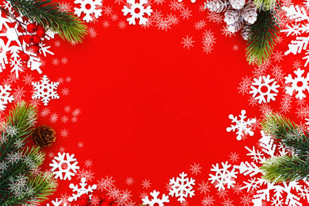 Christmas background with xmas tree branches and snowflakes on red canvas background. Merry christmas card. Happy New Year. Space for text Stock Photo
