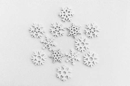 Christmas pattern in the form of snowflakes lined with small snowflakes on a white sparkling snow background