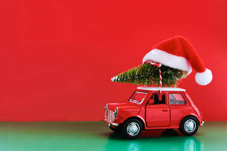 Minimal design for celebrating christmas or new year greeting card. Gift delivery concept. Little red toy car, Christmas tree and Santa hat on a red background