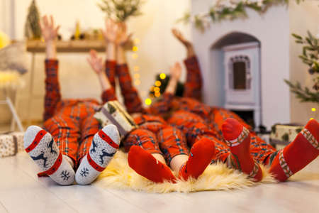 Feet in Christmas socks near fireplace. Happy family lying on bed. Mother, father and child having fun in Christmas time. Man, woman and kid relaxing at home. Winter holiday Xmas and New Year concept