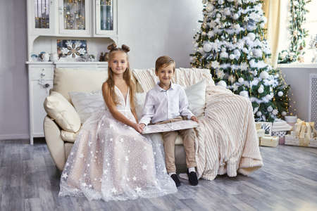 Happy smartly dressed little kids sitting on sofa with book in living room with Christmas tree
