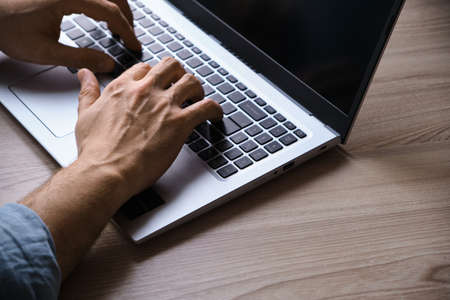 Man's hands typing on laptop keyboard. Cropped image of a young man working