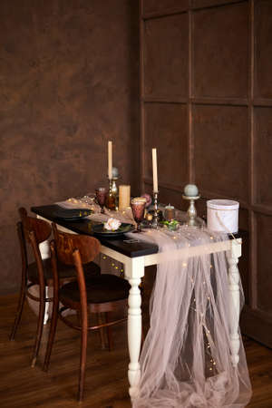 Romantic or Wedding dinner setup or Holiday table setting, brown, pink and gold decoration with candles and garland light.