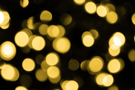 Defocused bokeh christmas big gold lights on black background. Blurred abstract gold glitter texture. Gold bokeh glitter wallpaper for Christmas, New year or festival background.