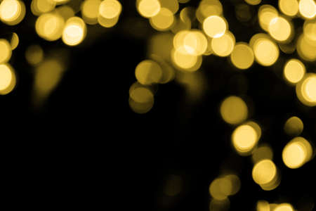 Defocused bokeh christmas big gold lights in the upper right corner on black background. Blurred abstract gold glitter texture. Gold bokeh glitter wallpaper for Christmas, New year or festival background.