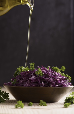 Sliced fresh red cabbage salad in wooden bowl. Pour olive oil. Space for text.