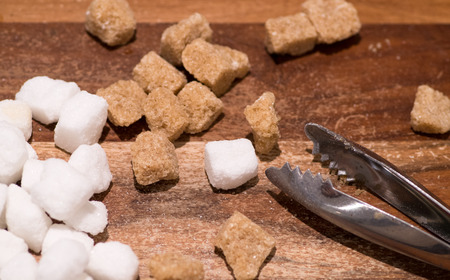Brown cane and white sugar cubes isolated on wooden background and sugar tongs.