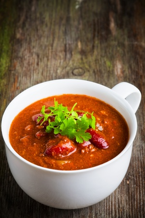A cup of chili con carne with coriander photo