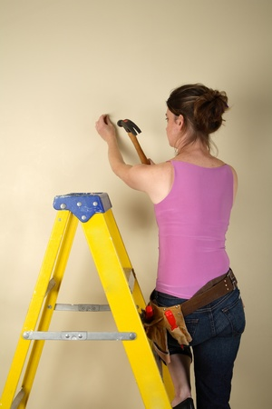 step ladder: Young woman standing on a step ladder about to hammer a nail into a wall