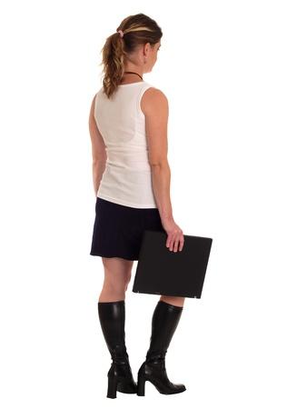 Jeune femme marchant loin de la cam�ra tenant un ordinateur portable. Banque d'images