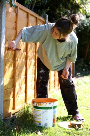 Wooden fence being painted by a young woman