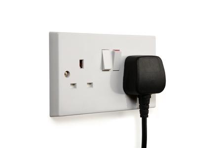 British socket and black plug. Socket turned on.