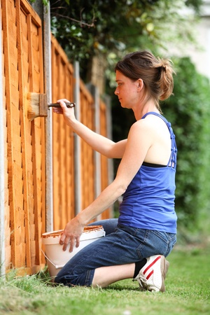 Young woman painting the fence in a garden