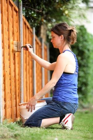 Joven pintura la valla en un jardín