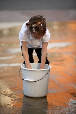 Young girl with her hand in a bucket of water Stock Photo - 9022138