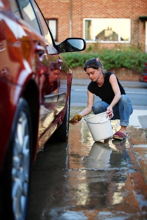 Young woman washing the wheel of a red car photo