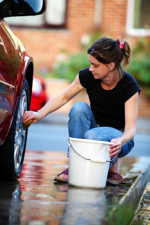 seau d eau: Young woman washing the wheel of a red car