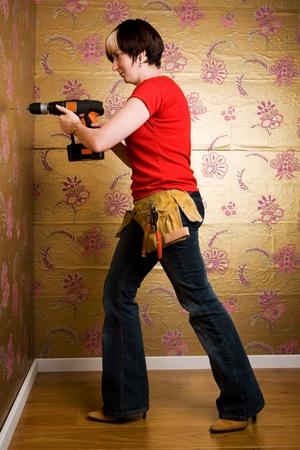Jeune femme adulte percer un trou dans un mur Banque d'images