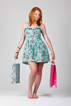 Femme rousse tenant sacs � provisions