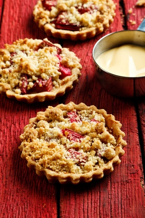 Rhubard crumble tarts with custard on a red wooden background Stock Photo