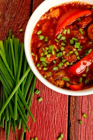 Chorizo stew on a red wooden background