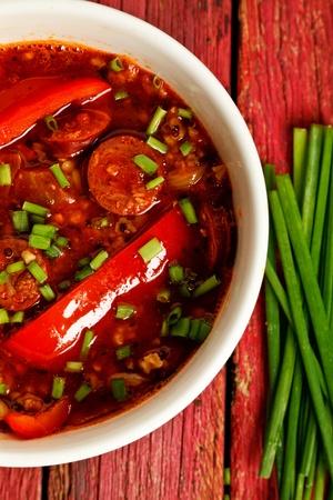 chorizo: Chorizo stew on a red wooden background