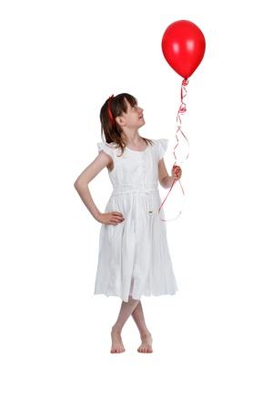 Jeune fille tenant un ballon rouge sur un fond blanc Banque d'images