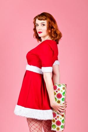 Femme tenant un cadeau de Santa sur un fond rose