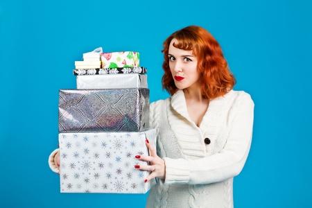 Femme rousse sur un fond bleu tenant ses cadeaux de No�l Banque d'images