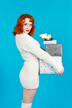 long socks: Redhead woman on a blue background holding her Christmas presents Stock Photo