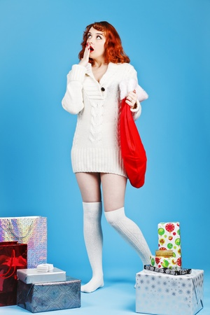 Redhead woman on a blue background hold her Christmas stocking photo