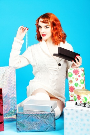 long socks: Redhead woman on a blue background opening her Christmas presents Stock Photo