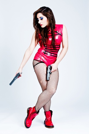 latex woman: Red latex woman with handguns on a grey background