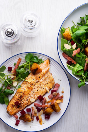 Pan-fried trout with bacon, beetroot and almonds salad Stock Photo