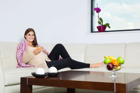 Smiling pregnant woman with a glass of orange juice photo