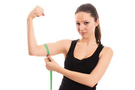 bicep: Disappointed woman measuring bicep Stock Photo