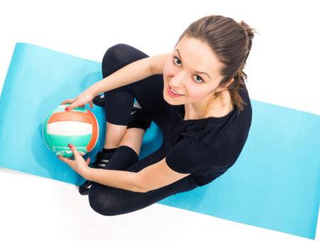 pelota de voley: Colocar la mujer con voleibol sentado en la estera del ejercicio Foto de archivo